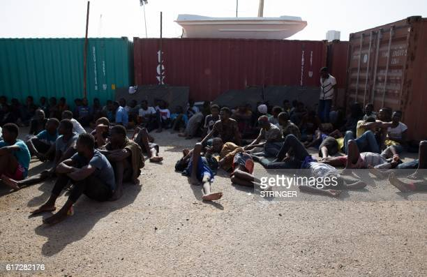 TOPSHOT Migrants who were rescued by Libyan forces rest at Tripoli Commercial Port before being transported to a detention centre in the Libyan...