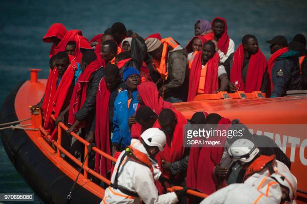 Migrants who were rescued from a dinghy in the Mediterranean Sea stand aboard rescue boat after their arrival at Port of Malaga Members of the...