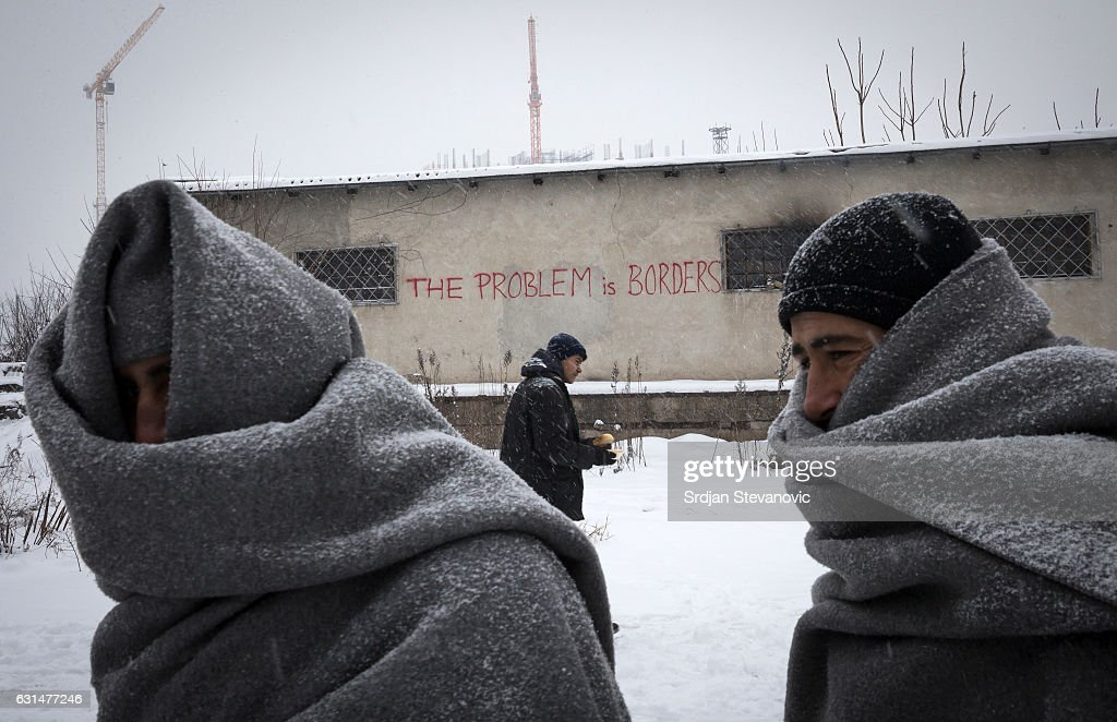 Migrants wrap themselves in blankets as they wait in line to receive free food as snow falls outside a derelict customs warehouse on January 11, 2017 in Belgrade, Serbia. It is estimated that around 1, 000 migrants are sleeping rough in Serbia, enduring temperatures as low as 20 degrees celcius.
