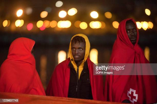 Migrants wrapped with red blankets stand on a rescue boat after their arrival at Malaga Port. An intensive border patrol by Moroccans authorities has...
