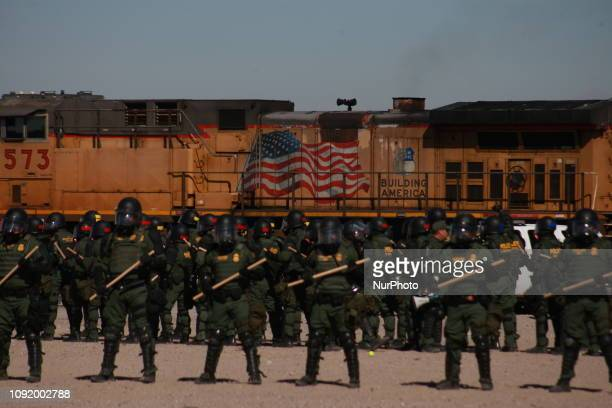 Migration agents carry out migrant containment exercises on the border between Ciudad Juarez and Paso Texas behind the agents crosses a train with an...