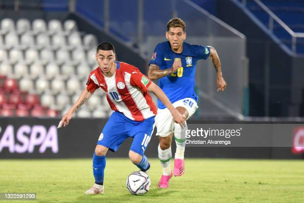 Miguel Almirón of Paraguay competes for the ball with Roberto Firmino of Brazil during a match between Paraguay and Brazil as part of South American...
