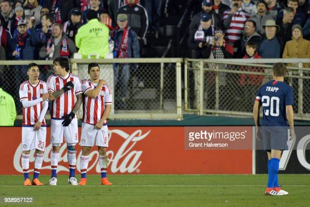 Miguel Almiron Federico Santander and Rodrigo Rojas of Paraguay defend a direct kick by Wil Trapp of United States during their game at WakeMed...
