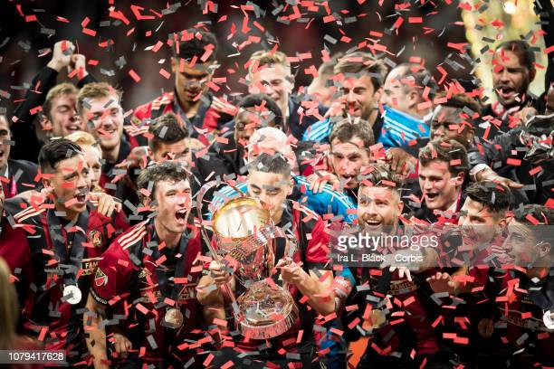 Miguel Almiron of Atlanta United kisses the Phillip P Anschutz MLS Championship Trophy in celebration with other teammates after the 2018 Audi MLS...