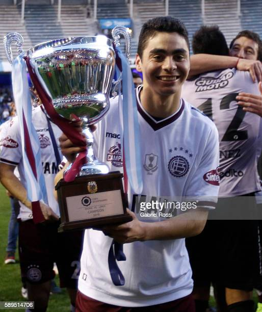 Miguel Almiron of Lanus celebrates with the trophy after winning the match between Racing Club and Lanus as part of Copa del Bicentenario de la...