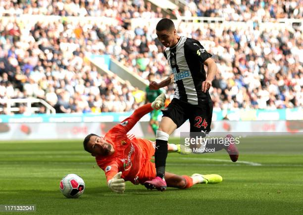 Miguel Almiron of Newcastle United is challenged by Ben Foster of Watford during the Premier League match between Newcastle United and Watford FC at...
