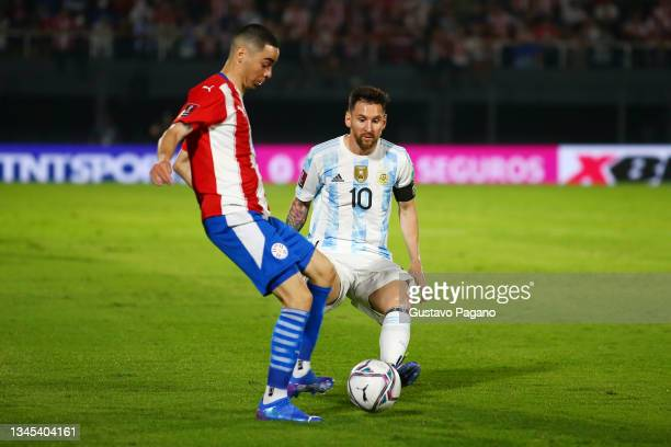 Miguel Almiron of Paraguay and Lionel Messi of Argentina fight for the ball during a match between Paraguay and Argentina as part of South American...