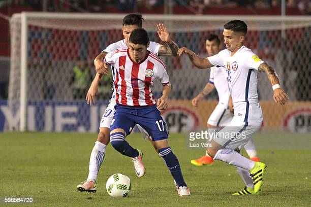Miguel Almiron of Paraguay dribbles past Charles Aranguiz and Felipe Gutierrez of Chile during a match between Paraguay and Chile as part of FIFA...