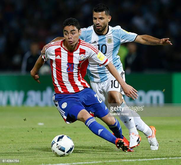 Miguel Almiron of Paraguay drives the ball while followed by Sergio Aguero of Argentina during a match between Argentina and Paraguay as part of FIFA...