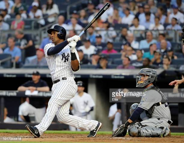 Miguel Andujar of the New York Yankees hits a solo home run as Michael Perez of the Tampa Bay Rays defends in the second inning at Yankee Stadium on...