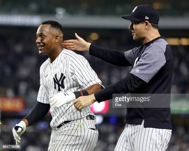 Miguel Andujar of the New York Yankees is congratulated by manager Aaron Boone after the win over the Cleveland Indians at Yankee Stadium on May 4...