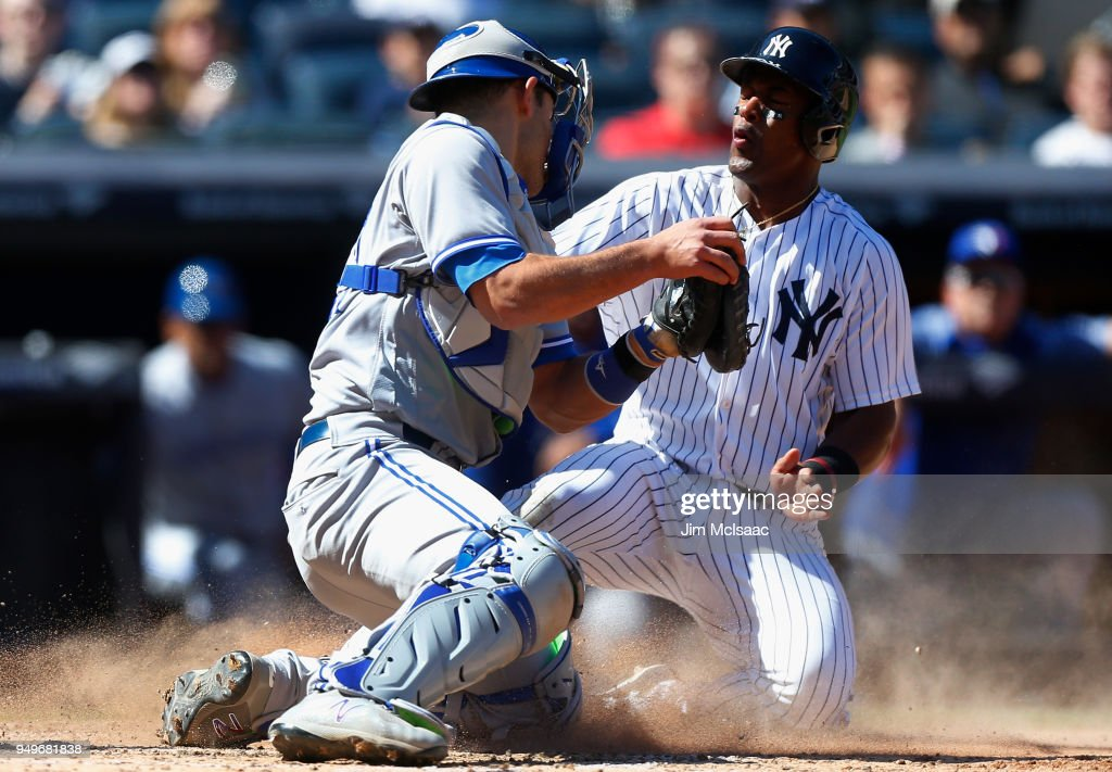 Miguel Andujar #41 of the New York Yankees scores a run against Luke Maile #21 of the Toronto Blue Jays after a sacrifice fly in the sixth inning at Yankee Stadium on April 21, 2018 in the Bronx borough of New York City.