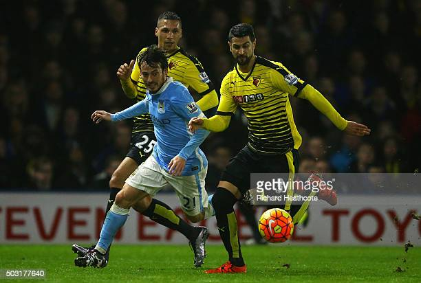 Miguel Angel Britos of Watford battles for the ball with David Silva of Manchester City during the Barclays Premier League match between Watford and...