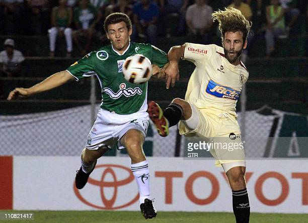 Miguel Angel Hoyos of Bolivian Oriente Petrolero vies for the ball with Juan Gonzales Vigil of Peruvian Leon Huanco during a Libertadores Cup...