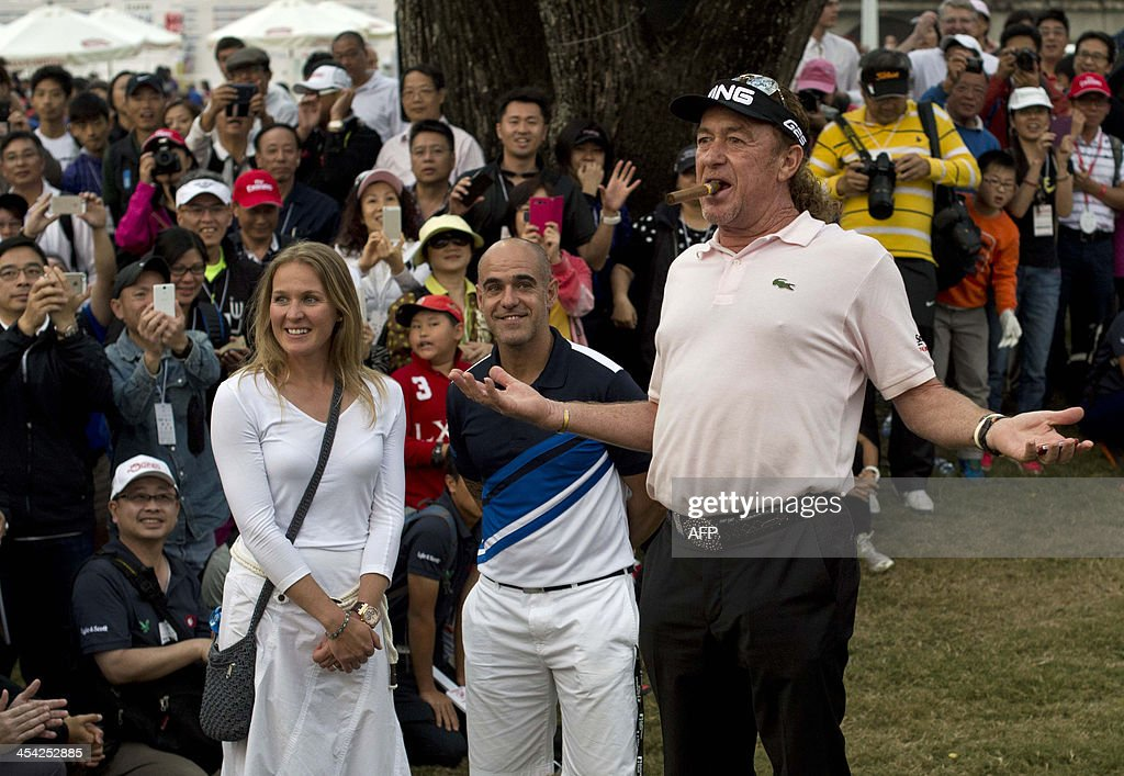 Miguel Angel Jimenez (R) of Spain asks the crowd for a lighter for his cigar after winning the Hong Kong Open at the Hong Kong Golf Club in Hong Kong on December 8, 2013.