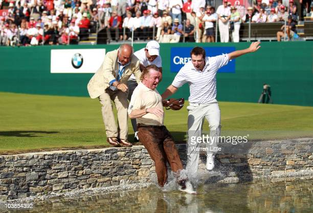 Miguel Angel Jimenez of Spain is pushed into the water by the 18th green by fellow Spanish players Pablo Larrazabal and Pablo Martin after winning...