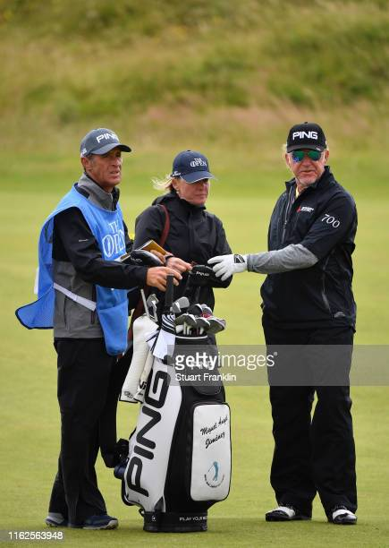 Miguel Angel Jimenez of Spain looks on with wife Susanna Styblo and his caddie during a practice round prior to the 148th Open Championship held on...