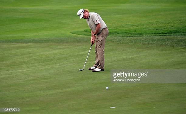 Miguel Angel Jimenez of Spain uses an iron to putt on the 18th green after breaking his putter during the second round of the Volvo Golf Champions at...