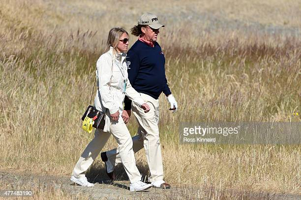 Miguel Angel Jimenez of Spain walks with his wife Susanne during a practice round prior to the start of the 115th US Open Championship at Chambers...