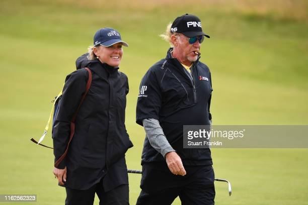 Miguel Angel Jimenez of Spain walks with wife Susanna Styblo during a practice round prior to the 148th Open Championship held on the Dunluce Links...
