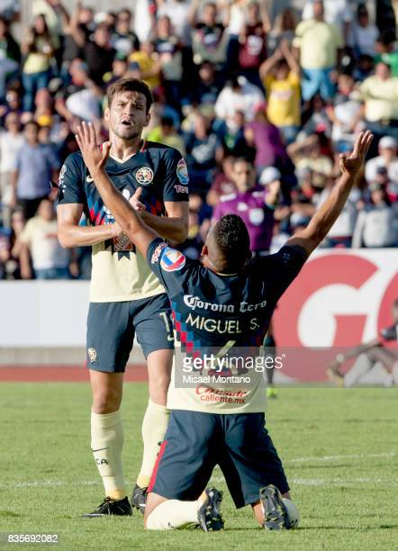 Miguel Angel Samudio of America celebrates the third goal of his team scored by Oribe Peralta during the fifth round match between Lobos BUAP and...