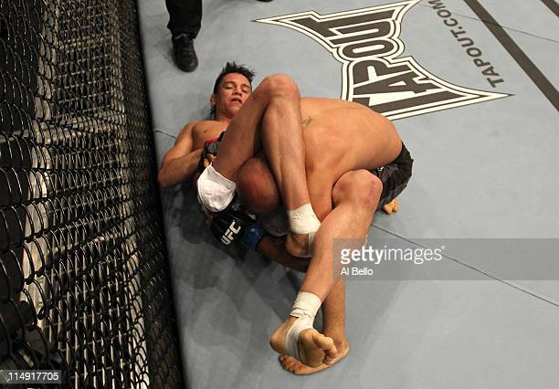 Miguel Angel Torres attempts a triangle choke submission against Demetrious Johnson during their bantamweight fight at UFC 130 at the MGM Grand...