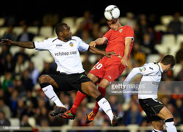 Miguel Brito of Valencia competes for the ball with Manu del Moral of Sevilla during the round 16 Copa del Rey 1st leg match between Valencia and...