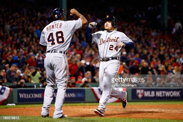 Miguel Cabrera and Torii Hunter of the Detroit Tigers celebrate scoring after Victor Martinez hit a single to deep left center against Franklin...