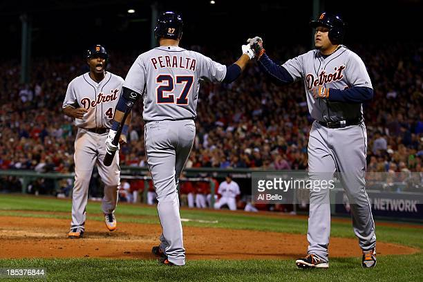 Miguel Cabrera and Torii Hunter of the Detroit Tigers celebrate with teammate Jhonny Peralta after scoring on Victor Martinez single to deep left...