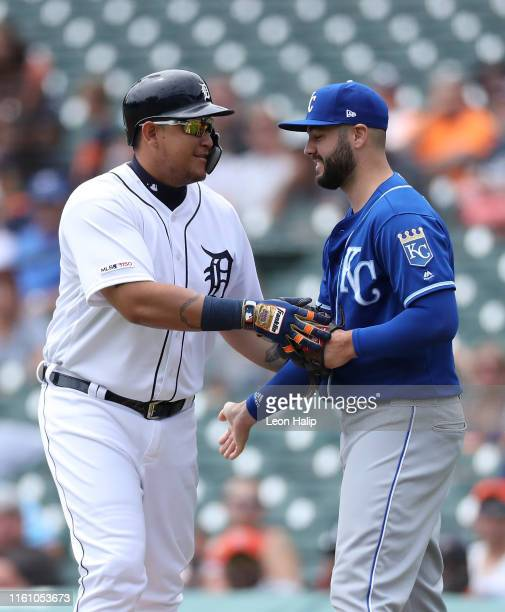 Miguel Cabrera of the Detroit Tigers and Cheslor Cuthbert of the Kansas City Royals meet at first base during the first inning of the game at...
