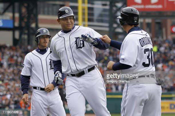 Miguel Cabrera of the Detroit Tigers celebrates at home plate after scoring on a Victor Martinez RBI double with Magglio Ordonez and Will Rhymes...