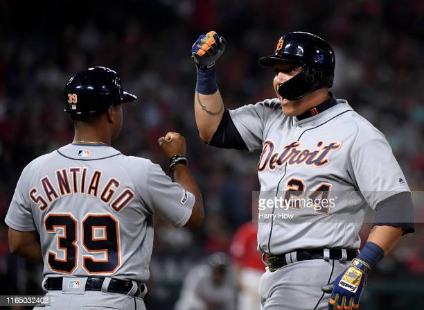 Miguel Cabrera of the Detroit Tigers celebrates his two run single with first base coach Ramon Santiago, to take a 5-2 lead over the Los Angeles...