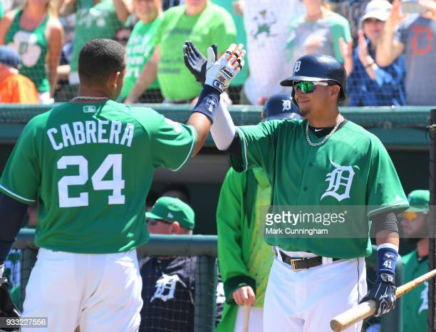 Miguel Cabrera of the Detroit Tigers gets a highfive from teammate Victor Martinez after hitting a home run in the first inning of the Spring...