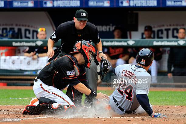 Miguel Cabrera of the Detroit Tigers gets tagged out at home plate by Caleb Joseph of the Baltimore Orioles on a double to deep center field hit...