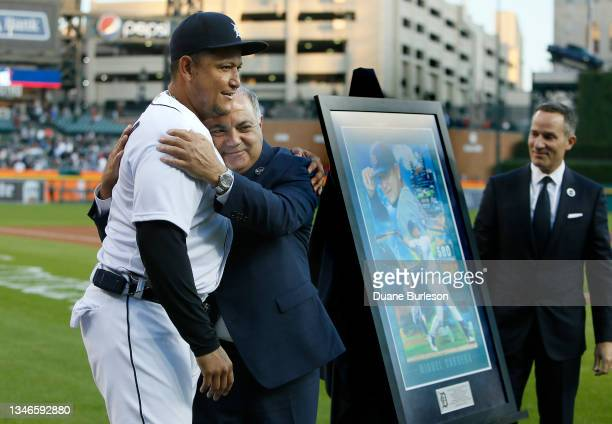 Miguel Cabrera of the Detroit Tigers is hugged by general manager Al Avila with Detroit Tigers Chairman and CEO Christopher Ilitch, right, looking on...