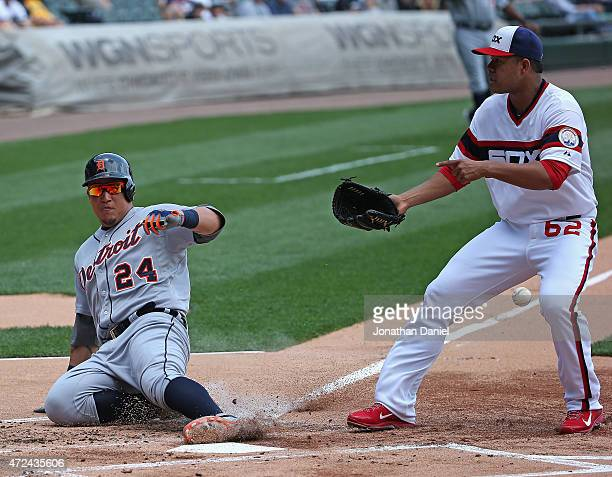 Miguel Cabrera of the Detroit Tigers scores a run in the first inning when Jose Quintana of the Chicago White Sox can't handle the throw at US...