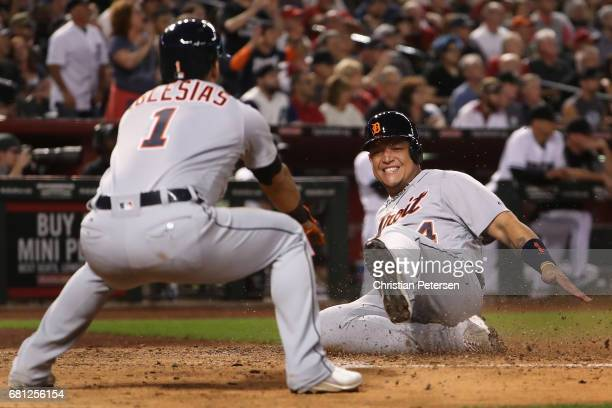 Miguel Cabrera of the Detroit Tigers slides into home plate to score a run alongside Jose Iglesias during the fifth inning of the MLB game against...
