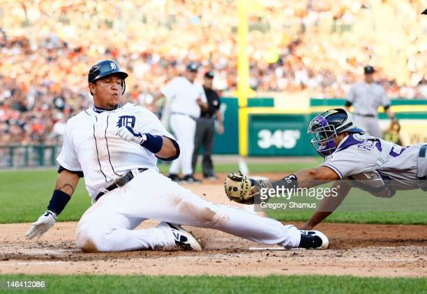 Miguel Cabrera of the Detroit Tigers slides under the tag of Wilin Rosario of the Colorado Rockies to score a third inning run at Comerica Park on...