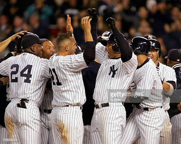 Miguel Cairo and Bernie Williams of the New York Yankees celebrate a win in the 12th inning over the Minnesota Twins 76 in Game 2 of the American...