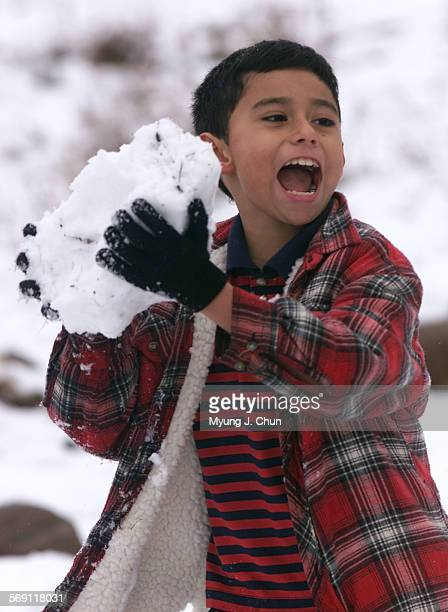 Miguel Carrillo gets an unfair advantage during a snowball fight in the front yard of his Shannon Valley Road home in Acton on Friday morning His K–2...