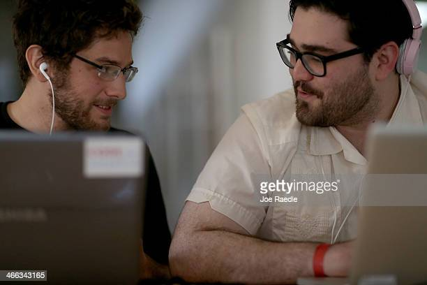 Miguel Chateloin and Lazaro Gamio use their computers to write code that would allow people living in Cuba to use email to post to blogs during the...
