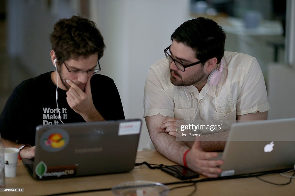 Miguel Chateloin (L) and Lazaro Gamio use their computers to write code that would allow people living in Cuba to use email to post to blogs during the Hackathon for Cuba event on February 1, 2014 in Miami, Florida. The hackathon brought together experts and programmers to devise innovative technology solutions aimed at strengthening communications and information access in Cuba. The event is organized by Roots of Hope with support from the John S. and James L. Knight Foundation.