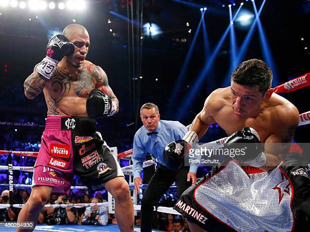 Miguel Cotto of Puerto Rico knocks Sergio Martinez of Argentina into the ropes during the first round as they battle for the WBC Middleweight...