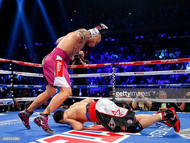 Miguel Cotto of Puerto Rico knocks Sergio Martinez of Argentina to the canvas during the first round as they battle for the WBC Middleweight...