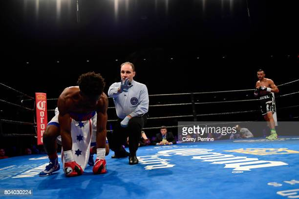Miguel Cruz knocks down Alex Martin in the first round as referee Gary Rosato counts in the first round during a main event welterweight bout at the...