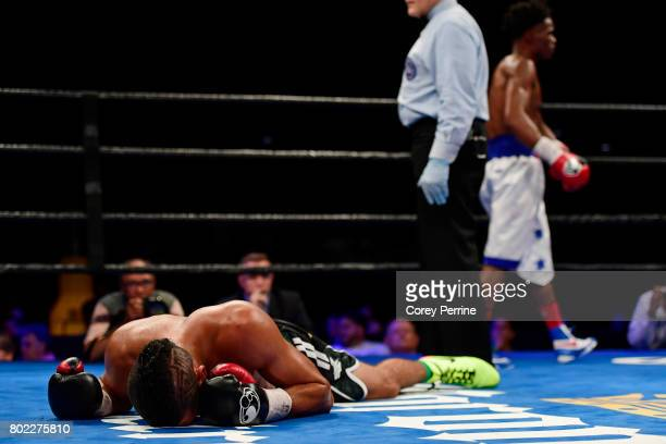 Miguel Cruz lays on the canvas after a blow below the waist has him wincing in pain as referee Gary Rosato sends Alex Martin to a corner in the fifth...
