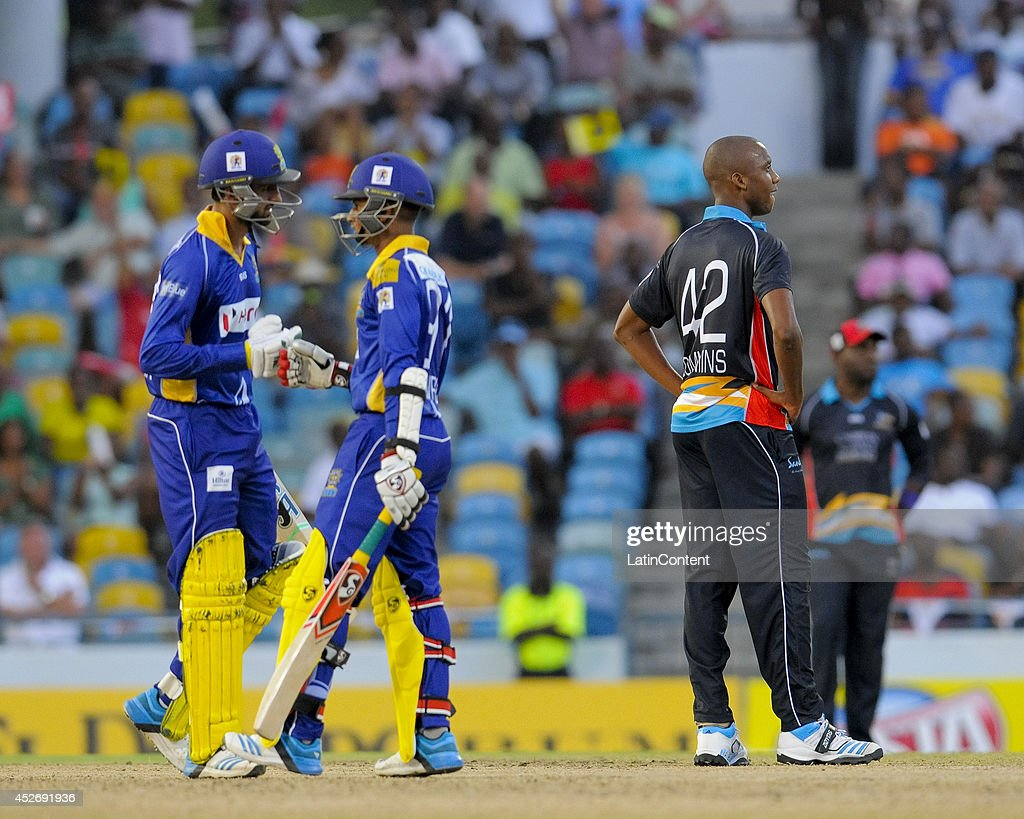 Miguel Cummins (R) of Antigua Hawksbills watches the ball cross the boundary as Shoaib Malik (L) and Shane Dowrich (C) of Barbados Tridents knock gloves during a match between Barbados Tridents and Antigua Hawksbills as part of the week 3 of Caribbean Premier League 2014 at Kensington Oval on July 25, 2014 in Bridgetown, Barbados.