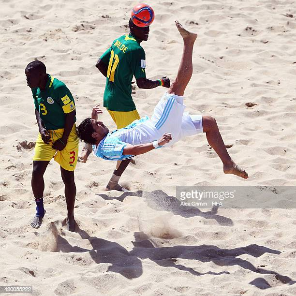 Miguel de Ezeyza of Argentina does an overhead kick against Ngalla Sylla and Ibrahima Balde of Senegal during the FIFA Beach Soccer World Cup...