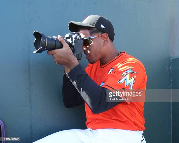 Miguel Del Pozo of the Miami Marlins picks up a camera and takes photos of teammates while sitting in the dugout during a spring training game...