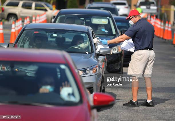 Miguel Diaz who works for the City of Hialeah hands out unemployment applications to people in their vehicles in front of the John F Kennedy Library...